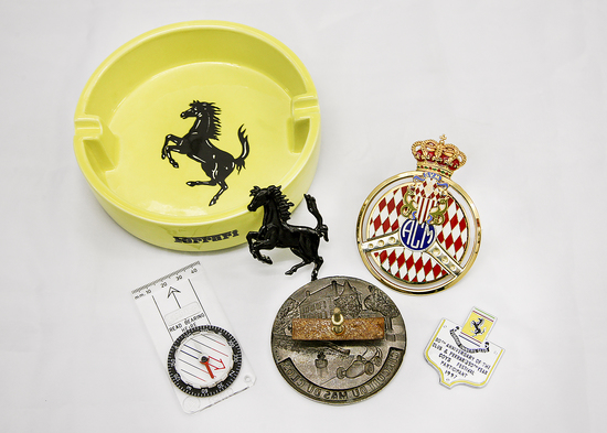 Collection of car badges and Ferrari ash tray