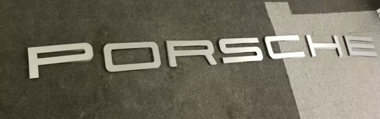 A large font-correct Porsche hanging wall sign
