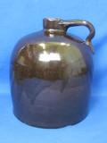 """Brown Stoneware Jug - - 9"""" tall – Chip on bottom – Wear around rim"""