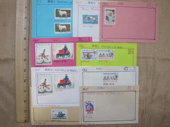 Lot of 13 unused 1960s Mali postage stamps, attached at the top to pieces of construction paper.