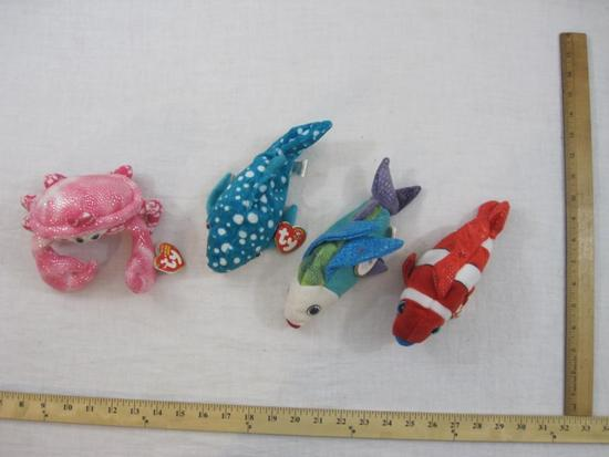 Four TY Beanie Babies including Propeller, Jester, Poseidon, and Sunburst, all tags included and