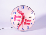 CIRCA 1940S-50S SEALED POWER PISTON RINGS LIGHT-UP CLOCK