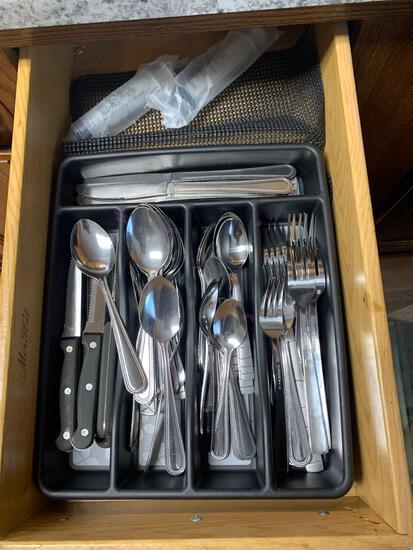 Drawer full of eating utensils knives spoons forks plus