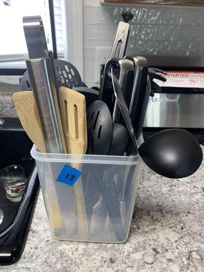 Container full of serving tongs spatula?s soup ladles pasta spoons plus