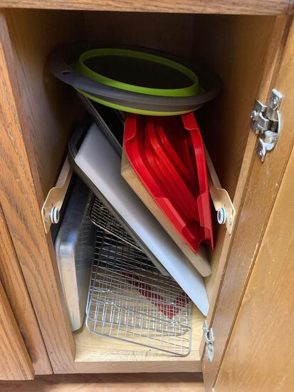 Cabinet containing cutting boards pizza pans strainers drying racks