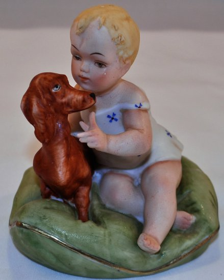 Porcelain little girl with Dachshund dog on pillow