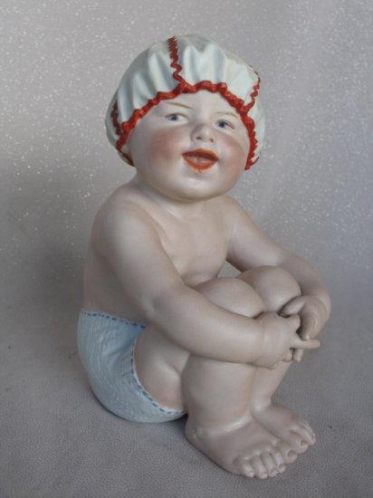 "Lot 24. Allbisque 1912 Gebruder Heubach ""Piano Baby"" sitting figure 22cm wi"