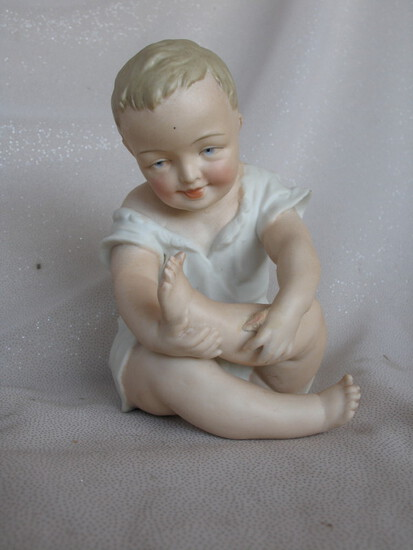 Three Figurines:- Bisque Heubach type 15cm seated boy with crossed legs inc