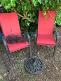 TWO RED PATIO CHAIRS, A METAL UMBRELLA STAND AND METAL BASKETS