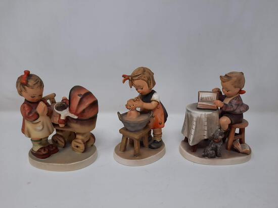 3 Hummels - Doll Bath, 319; Girl Praying with Baby Carriage, 67; Boy Reading Book by Table, 206