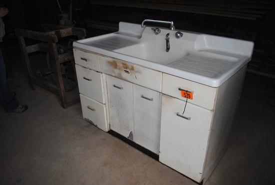 White porcelain sink & steel wheel encased in wood frame