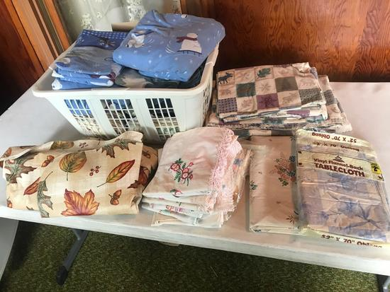 Various table cloths, flannel sheets, and decorative crocheted pillow cases.