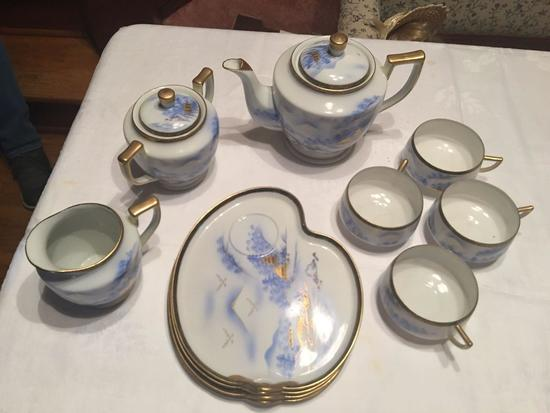 4 place setting of tea snack set, creamer, sugar, 4 plates with cups , and one teapot.