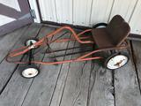 Pedal-car frame (no outside tin work), includes 4 steel wheels w/rubber, steel seat, and pedals.