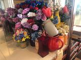 Various artificial flowers, planters and water pitchers.