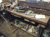 Wooden workbench With misc contents, with vise, work light and more.