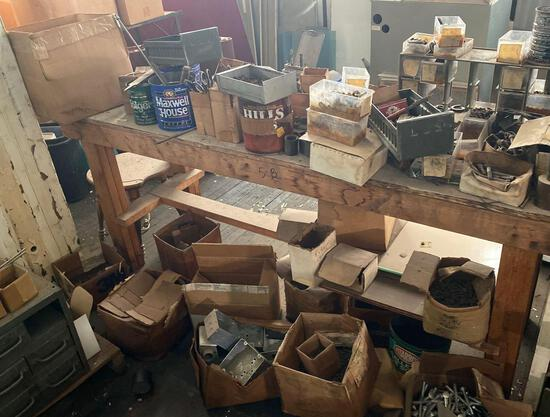 Misc nuts and bolts, some rusted, wooden workbench included.