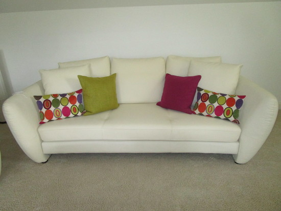 Beautiful White Leather Sofa w/Bright Cloth Covered Accent Pillows.