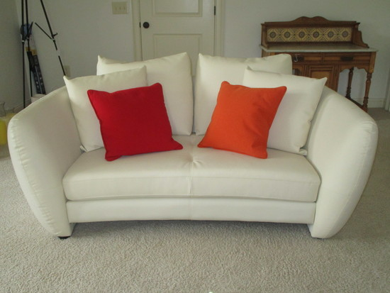 White Leather Loveseat w/Red & Orange Accent Pillows.  Some pricks on arms.