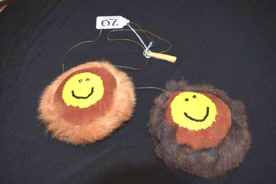 Handmade pair of round face pendants of seal fur on cord to hang from neck