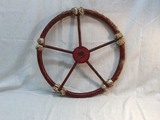 Antique rope wrapped metal ships wheel