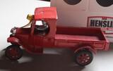 RED CAST IRON TRUCK WITH MAN, HAS PAINT CHIPS