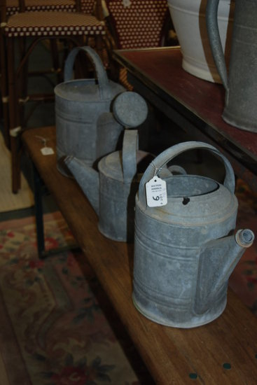 Group of three small watering cans