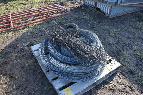 Pallet of used barbed wire w/ coiled fence stays