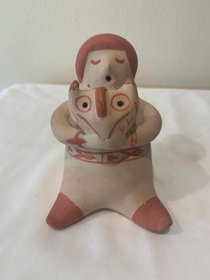 Red on cream seated figure holding an Owl