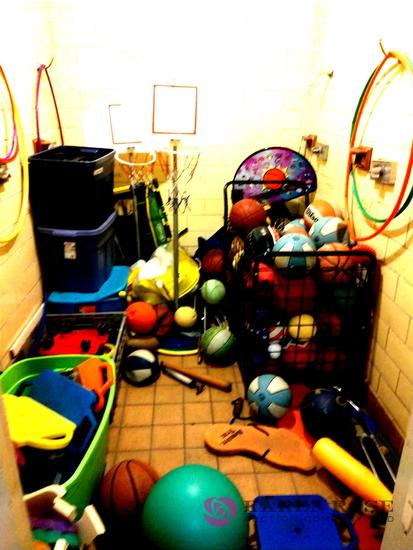 Room with a lot of basketballs, hoops, and sporting goods for kids