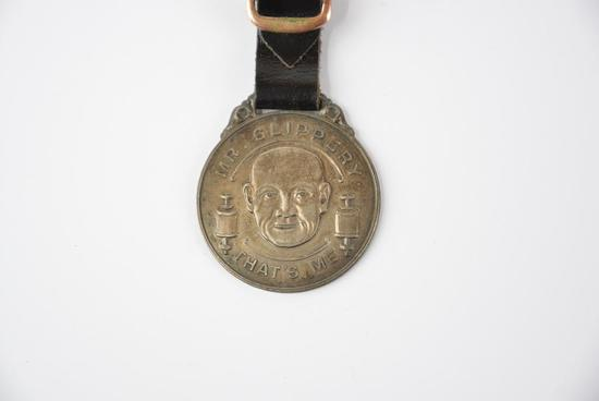 """The Advance Grease & Chemical Co. """"Mr. Slippery"""" metal watch fob"""
