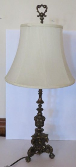 Ornate metal table lamp with faces and clawfeet