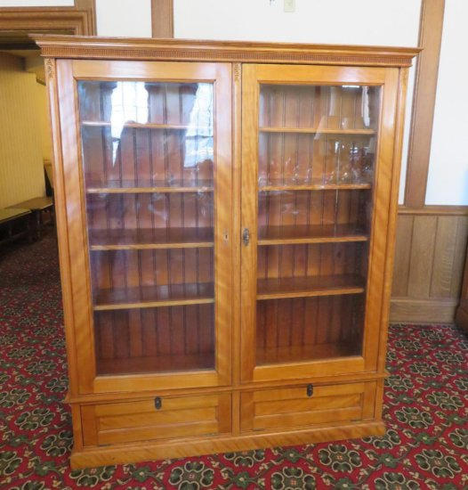 Beautiful maple two door bookcase with two drop down doors and carving