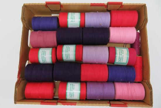 "20 spools of Mayville carpet warp, purple, pinks and reds, 4"" tall"