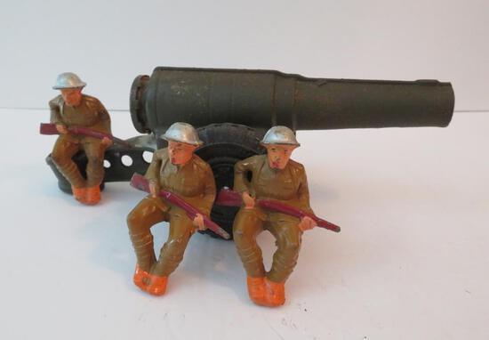 Cast iron carbide cannon and three seated soldiers