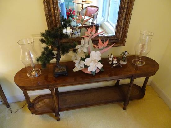 All items on table: floral arrangement, hurricane lamps, artificial tree, birds.
