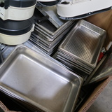 crate of stainless pans, sheet pans, TP holders, etc