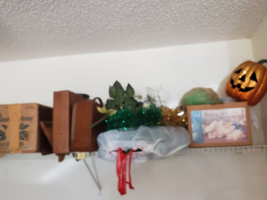 mixed Christmas and holiday decorations on garage shelf