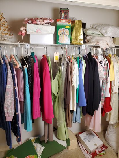 mixed holiday décor and ladies clothing stored in guest bedroom closet