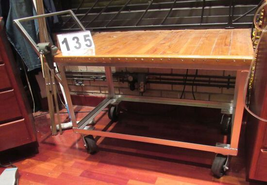 steel framed work table on casters with small vise and varnished wood top