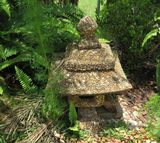 Asian masonry house covered with inset pebbles lawn ornament