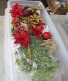 clear plastic storage tote of Christmas florals and décor
