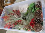 clear plastic storage tote of Christmas florals & decor
