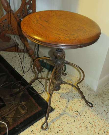 antique piano stool with cast metal legs and oak seat