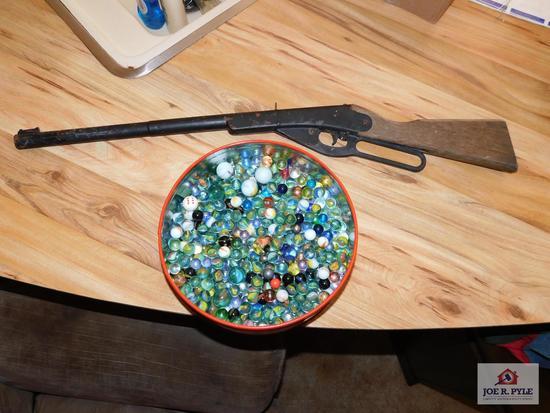 Tin of marbles & a Daisy BB gun