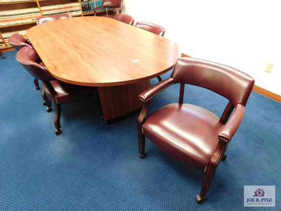 Oval conference table with 9 burgundy chairs with rollers