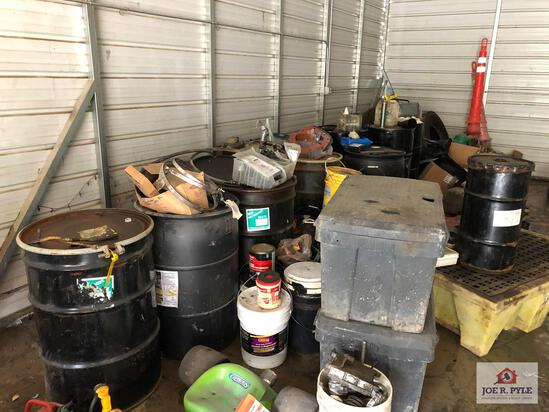 Contents of left side wall: oil drums, drain pans, gas cans, etc.