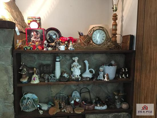Lot of decorator items on shelf and above mantle: clocks, statues, vases, lamps, etc.
