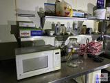 Contents of prep table: microwave, supplies, dishes, metal baskets, etc