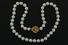 PEARLS:  [1] Single strand of Mikimoto 7.5 to 8.0 mm cultured pearls secured with a 24KYG rose on an